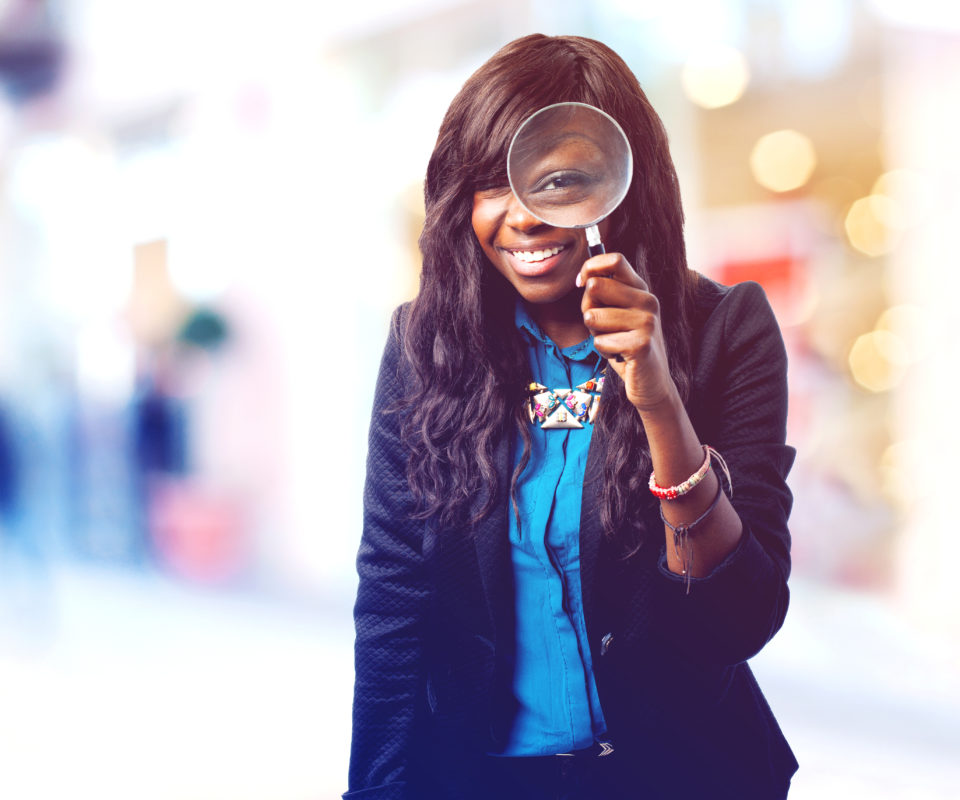 happy black woman with magnifying glass